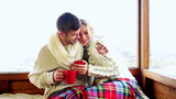 Cute couple relaxing under a blanket in their ski lodge