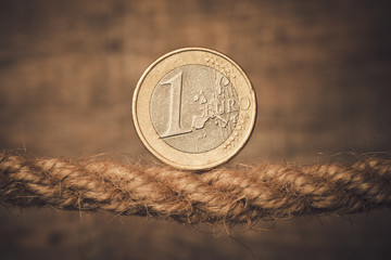 Euro entangled in a rope on wood background