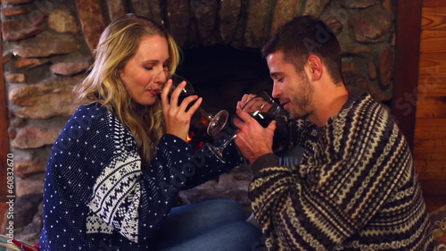 Couple celebrating christmas together in front the fireplace