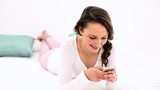 Smiling woman lying on bed texting on the phone