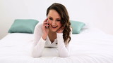 Smiling woman lying on bed talking on the phone