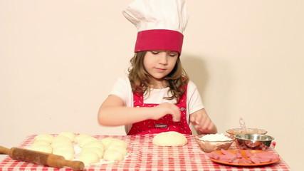 little girl cook kneading dough
