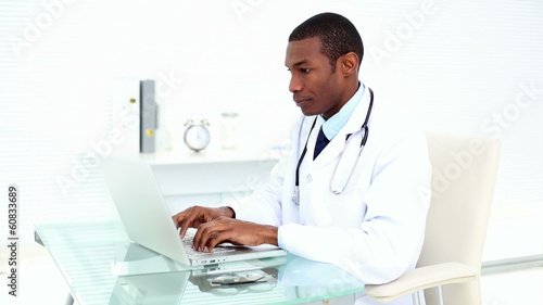 Serious doctor working on his laptop