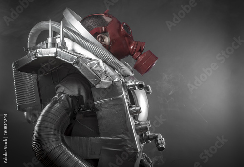 Astronaut with red gas mask on a black background with huge weap