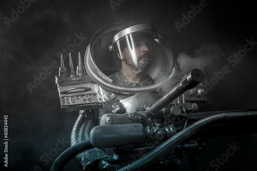 Strong Astronaut on a black background with huge weapon.