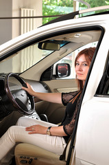 Female driver testing a new car at a showroom of dealer