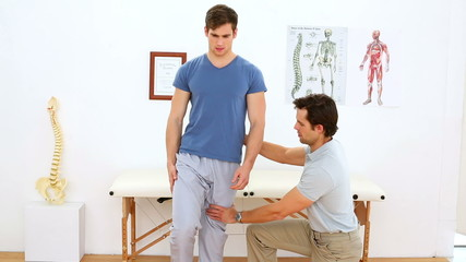 Physiotherapist checking knee of injured patient