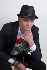 A young man with a rose.