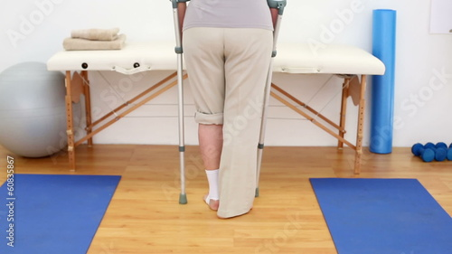 Injured patient in crutches walking away from camera