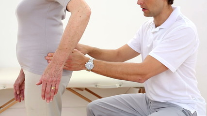 Physiotherapist touching senior patients hips