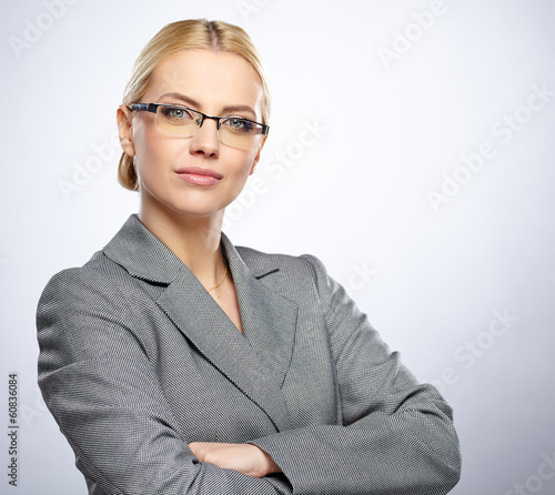 Portrait of a beautiful young business woman standing against gr