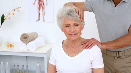 Physiotherapist stretching senior patients neck