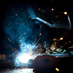 Welder in action with bright sparks.