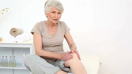 Injured patient rubbing her sore knee