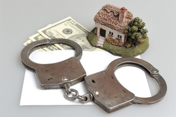 Handcuffs, toy house and white envelope with money on gray
