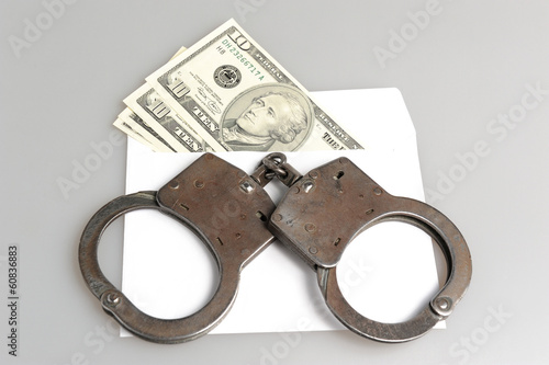 Handcuffs and white envelope with money on gray