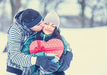 Teen couple with gift kissing in winter park.