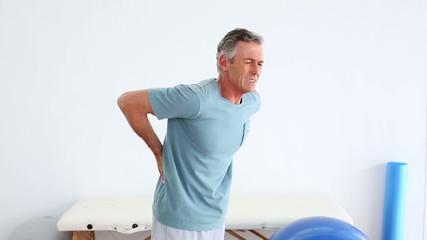 Mature patient rubbing his painful back