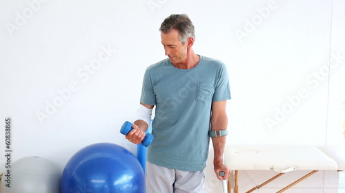 Injured patient on crutches lifting dumbbell