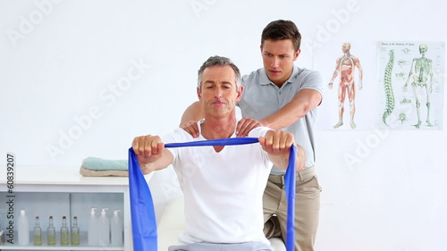Physiotherapist checking mature patient stretching