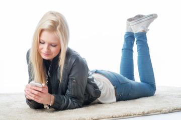 Blondes Mädchen simst mit Smartphone
