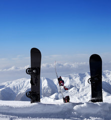 Three snowboards in snow near off piste slope in sun day