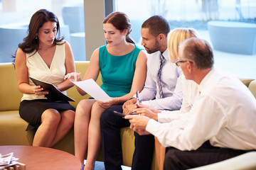 Group Of Businesspeople Having Meeting In Office Lobby