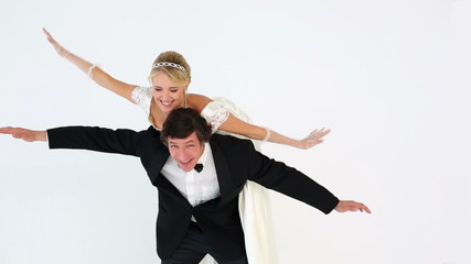 Groom carrying pretty new wife on his back