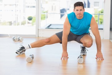 Full length portrait of a sporty man doing stretching exercise