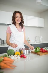 Portrait of smiling woman preparing food in kitchen