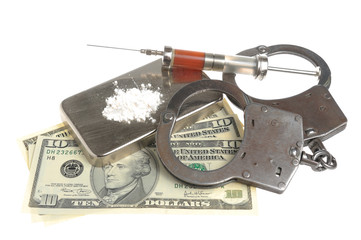 Drugs, syringe with blood, handcuffs and money isolated