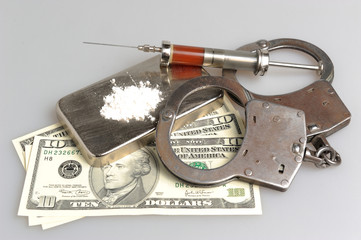 Drugs, syringe with blood, handcuffs and money on gray