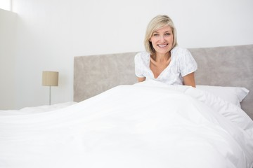 Pretty smiling woman sitting on bed