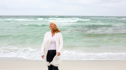 Retired woman walking by the sea