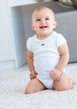 Cute cheerful baby sitting on carpet