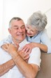 Loving senior woman embracing husband