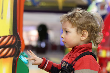 Kid playing on game machine