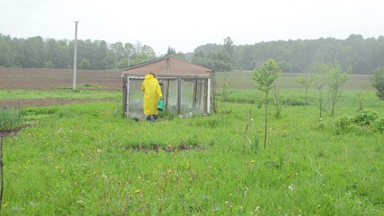 Woman water plants close greenhouse walk away with raincoat