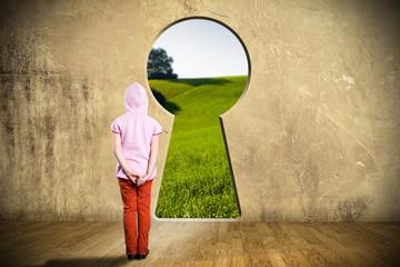 kleines Mädchen steht vor Schlüsselloch in einer Wand