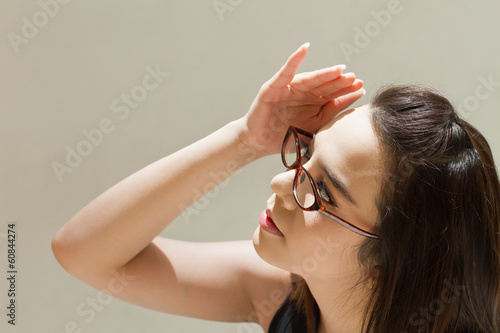 woman suffers from heat of strong sunlight, plain background