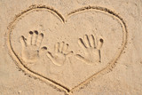 Drawing heart and family with kid hand print on sand.