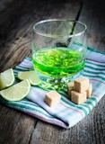 Glass of absinth with lime and sugar cubes poster