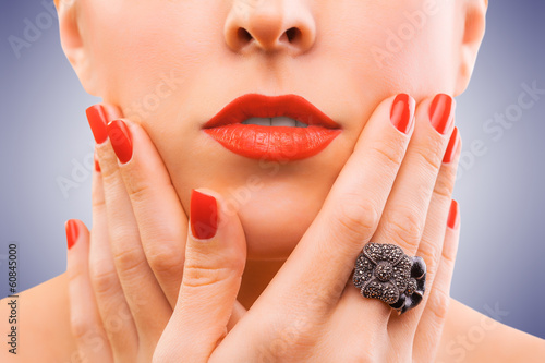 face and beautiful red manicure on the blue