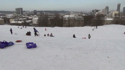 children slide with sledge down the hill. Winter time leisure.