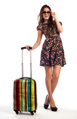 Full length of casual woman standing with travel suitcase