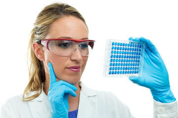 young researcher examining a microplate