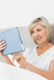 Mature woman using digital tablet in bed