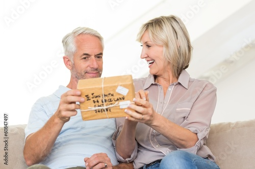 Smiling woman surprising mature man with a gift on sofa