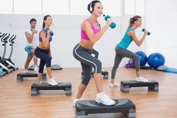 Class performing step aerobics exercise with dumbbells
