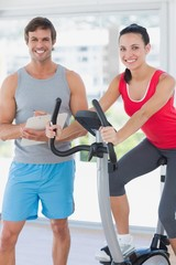 Woman with instructor working out at spinning class